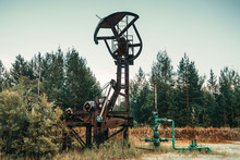 Old Rusty Pump Jack In The Oilfield Situated In The Beautiful Forest. Environmental Pollution. Oil And Gas Concept.