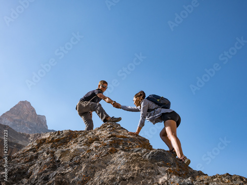 Fotografía  Helping hand couple hikers in mountains