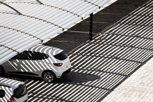 White Clean Cars On A Parking Lot In Sunny Summer Day Are Under The Shadows From The Canopy Falling On