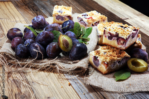 Obraz na plátně Rustic plum cake on wooden background with plums around.