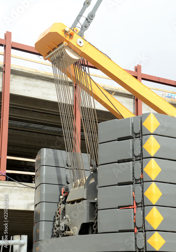 Foto  Counterweight and pulley blocks of a large construction crane.