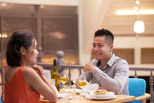 Cheerful young woman enjoying dinner and talk in restaurant