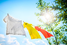 Photo Of Three T-shirts Hanging On Rope On Background Of Blue Sky With Treetops.