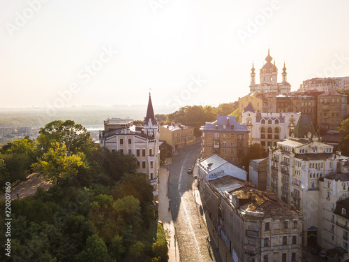 Photo Stands Kiev Andrew's Descent. Castle of Richard the Lionheart and St.Andrew's Church. Soft sunrise light. Morning in Kiev (Kiyv) Ukraine. Podil. Aerial drone photo