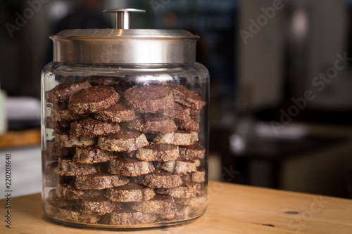 Foto Chocolate cookies neatly stacked up in a glass jar.