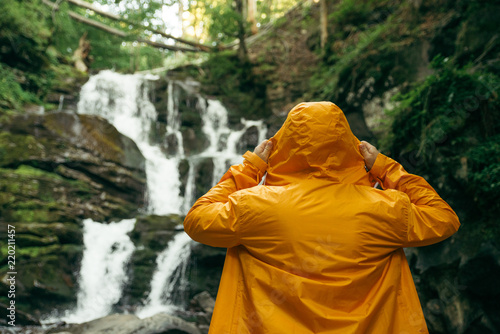 Fotografie, Obraz man standing in yellow raincoat and looking at waterfall