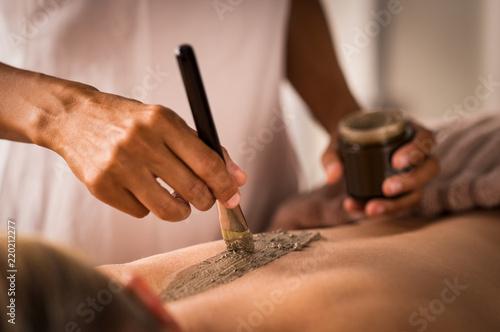 Fotografía  Beautician applying mud on body