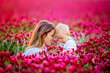 Leinwandbild Motiv Young mother, embracing with tenderness and care her toddler baby boy in crimson clover field, smiling happily
