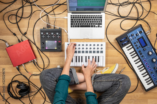 Woman making electronic music on laptop computer and digital instruments. Top view of young female producing modern indie music on synthesizer and digital controllers - 220224678