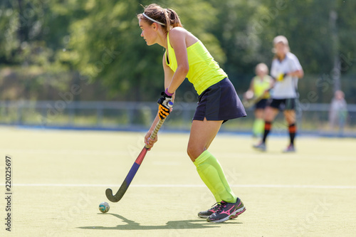 Young hockey player woman with ball in attack playing field hockey game