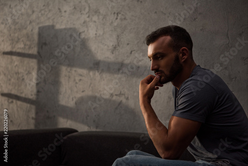 lonely pensive man sitting on sofa at home Canvas Print