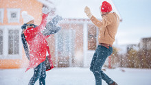 Young Couple Playfully Throws Snow In The Air, While Winter Snowfall Continues. Happy Man And Woman Playing With Snow In The Yard Of Their Idyllic House. Family Enjoying Winter.