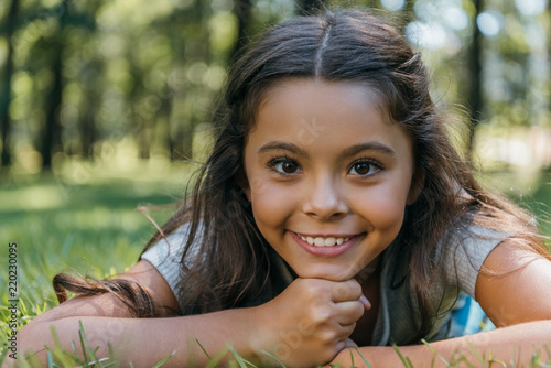 adorable happy child lying on grass and smiling at camera in park