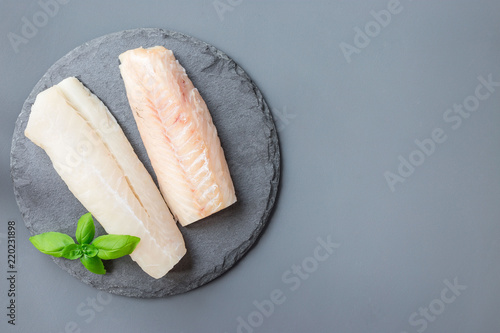 Canvas Print Fresh raw cod fillet with basil on stone plate, horizontal, copy space, top view