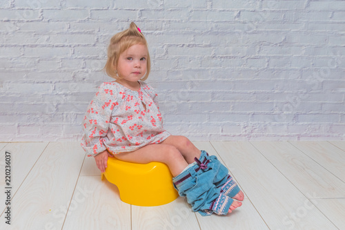 Photo a girl, baby sitting on a potty on a white brick wall background