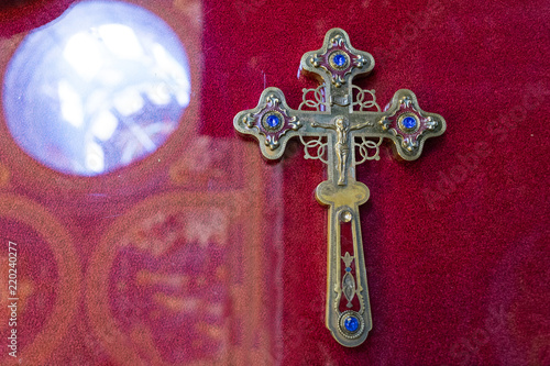Valokuva  a Christian cross of noble metal on a red background