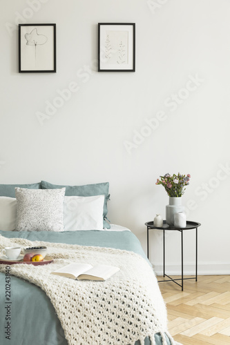 Fotografía  Pale sage and white linen, pillows and a blanket on a bed standing against white wall with two pictures in a bedroom interior