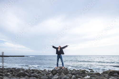 Photo Indie young caucasian woman standing with open arms and enjoy the nature and the freedom alone on the rocks at the beach