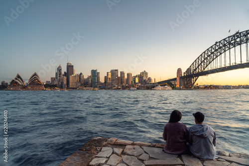 Canvas Print Romantic couple looks at Sydney skyline at dusk in Sydney New South Wales, Australia