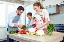 A Happy Family Is Preparing Vegetables In The Kitchen.