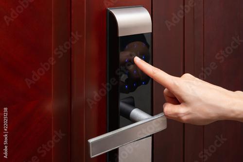 Zdjęcie XXL Pani wprowadzająca hasła do elektronicznego zamka do drzwi