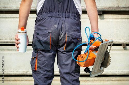 Fototapeta Construction worker with cup of coffee and electric saw obraz na płótnie