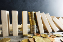 Financial Stability Concept With Pile Of Money Between Wooden Pieces With Domino Effect