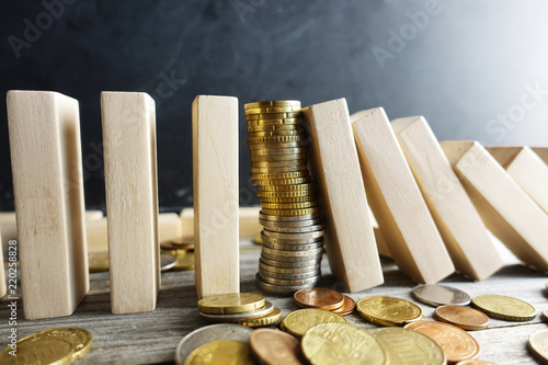 Fotografía  Financial stability concept with pile of money between wooden pieces with domino