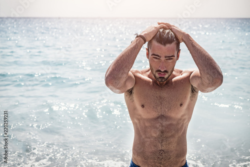 Fotografie, Obraz  Handsome muscular young man standing on a beach, relaxed, taking a bath, wearing