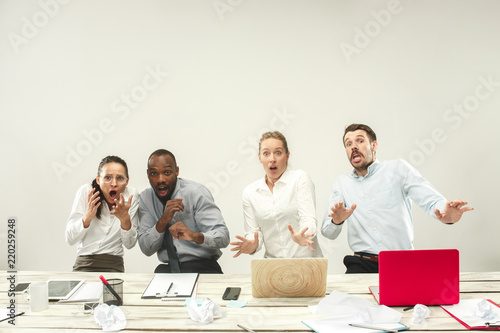Fototapeta Young upset frightened african and caucasian men and women sitting at office and working on laptops