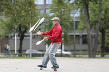 A Man In A Cap Juggles With Cl...