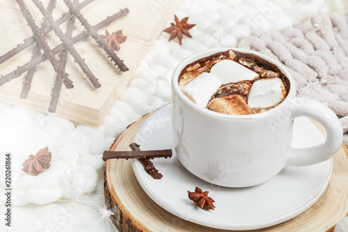 Cup of hot chocolate with marshmallows and candies in sun light. Sweet drink. Copy space.