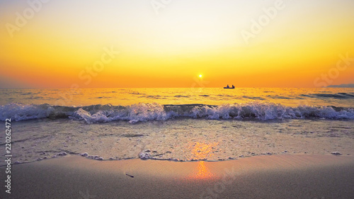 Fotografia Small boat of refugees sail on sea horizon against sunset seen from beach splash