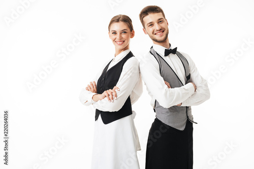 Young smiling waiter and waitress in white shirts and vests sstanding back to back while joyfully looking in camera with arms folded over white background