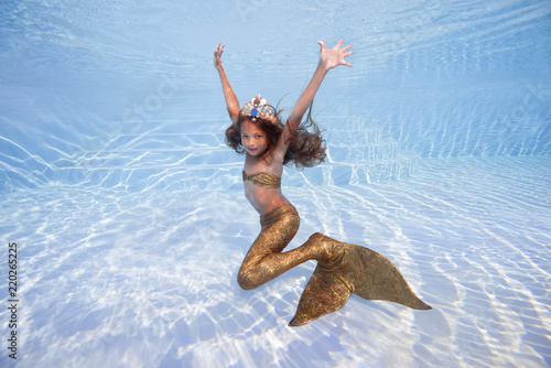 Photographie  A girl in a mermaid costume poses underwater in a pool