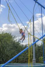 Girl Bungee Jumping In Trampol...