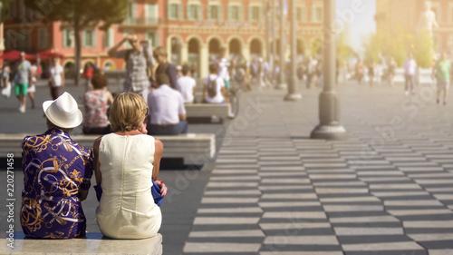 Fototapeta  Two women having rest on bench, active life in city center, sunny summer day