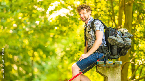 Fototapeta man hiker with backpack resting on bench in forest trail obraz