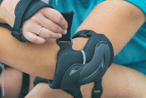 Woman rollerskater putting on elbow protector pads on her hand