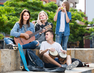 Portrait of four teenagers playing music together outdoors