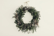 Modern Christmas Wreath. Stylish Rustic Christmas Wreath With Pine Cones,fir Branches,snow, Hanging On White Wall. Space For Text. Handmade Decor For Winter Holidays