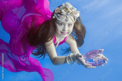 Fényképezés  Ggirl in long, purple dresses wearing poses underwater