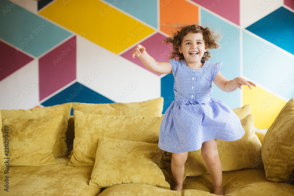 Fototapeta Cheerful little girl with dark curly hair in dress happily jumping on sofa at home