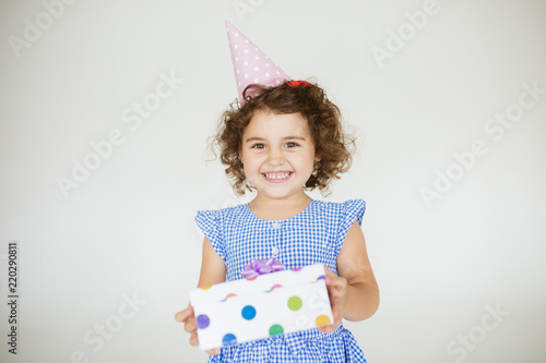 Fotografie, Obraz  Pretty baby girl with dark curly hair in dress and birthday cap happily looking