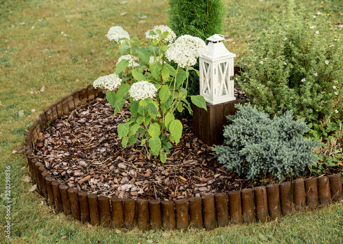Round flower bed covered by pine bark mulch and surrounded by brown weatherproof wood roll boarder palisade, inside are different plants, outdoors in summer Tapéta, Fotótapéta