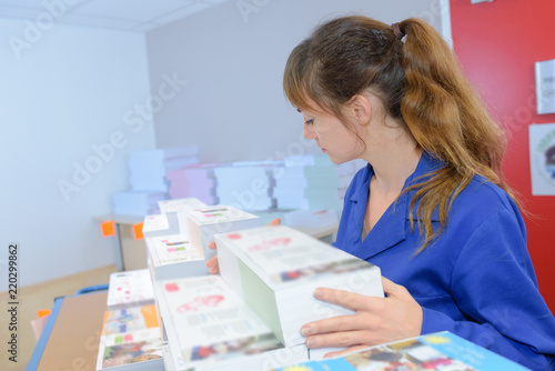 Woman with stacks of printed material