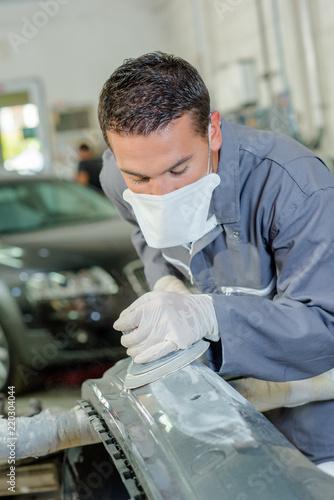 Mechanic sanding car bodywork Canvas Print