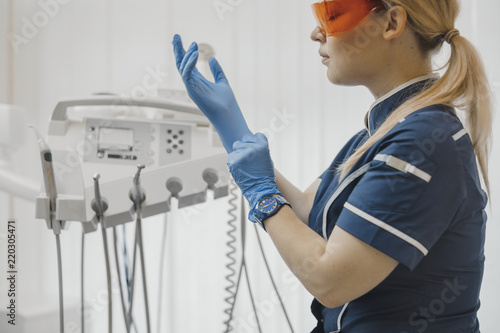 Fotomural Close up of dentist sitting next to dental equipment and putting on gloves