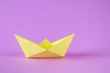 canvas print picture - Yellow paper boat from origami with an autumn leaf on a purple background.