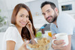 young happy couple having breakfast together with fruits and juice